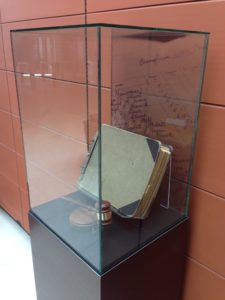 A glass case protecting the original ledger that  contains a page of signatures from 22 founding members of PSECU, as seen on the  print featured on the rear of the case.
